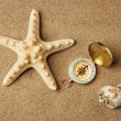 Compass and starfish on a sandy beach — Stock Photo