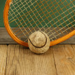 Old tennis ball and racket on a wooden floor — Photo