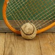 Old tennis ball and racket on a wooden floor — Stock Photo