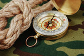 Compass and rope on a camouflage background — Stock Photo