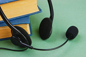 Headphones with a microphone and books — Stock Photo