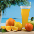 Glass of orange juice on a beach — Stock Photo