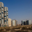 Sandy Desert and modern city in Sharjah UAE — Stock Photo