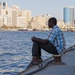 A young man sits on the waterfront in Deira Dubai , UAE — Stockfoto