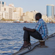 A young man sits on the waterfront in Deira Dubai , UAE — Stok fotoğraf