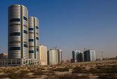 Desierto arenoso y la ciudad moderna en sharjah emiratos árabes unidos — Foto de Stock
