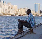 A young man sits on the waterfront in Deira Dubai , UAE — Stock Photo
