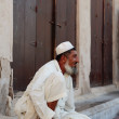 Old man sitting on the stone steps of the old city of Bar Dubai  — Stock Photo