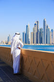 Arab man in national dress looks at the city of Dubai — Stock Photo