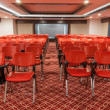 Rows of red chairs in empty conference hall — Stock Photo #37830319