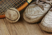 Old tennis ball with sneakers — Stock Photo