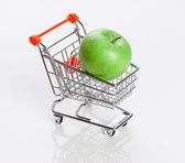 Green apple in shopping carts — Stock Photo