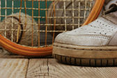 Old tennis ball and sneakers — Stock Photo