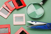 Old slides and a magnifying glass — Stock Photo