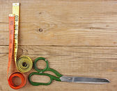Sartorial meter and scissors on the old wooden background — Stock Photo