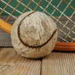 Old tennis ball and racket on a wooden floor — Stock Photo #41004033