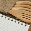 Wooden spoon and notebook on old wooden table — Stock Photo