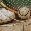 Stock Photo: Old tennis ball and sneakers on a wooden floor