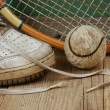 Old tennis ball and sneakers on a wooden floor — Stock Photo