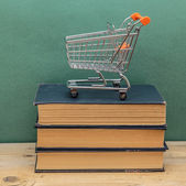 Stack of old books on a wooden shelf and shopping carts — Stock Photo