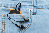 Player with headphones in the pocket of jeans — Stock Photo