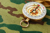 Compass on a camouflage background — Stock Photo