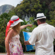 Woman and man looking at the map on a tropical landscape — Stock Photo