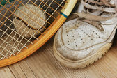 Old tennis ball and sneakers on a wooden floor — Stockfoto
