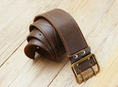 Leather belt with a buckle on a wooden board — 图库照片