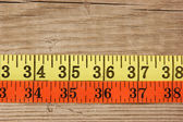 Sartorial meter on the old wooden background — Stockfoto