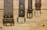 Leather belt with a buckle on a wooden board — Stock Photo