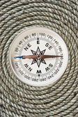 Compass on old twisted rope — Stock Photo