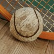 Old tennis ball and racket on a wooden floor — Stock Photo #43875547