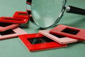 Stare slajdy i na zielony stół szkło powiększające — Zdjęcie stockowe