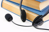 Headphones with a microphone and a stack of books  — Stock Photo