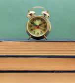 Old books and alarm clock — Stock Photo