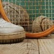 Old tennis ball and sneakers on a wooden floor — Stock Photo #47540161