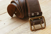 Leather belt with a buckle on a wooden board — Foto de Stock