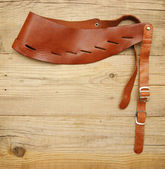 Leather strap with a buckle on a wooden board — Stock Photo