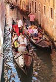 Tourists float in gondola on canal in Venice — 图库照片