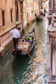 Tourists float in gondola on canal in Venice — Stock Photo
