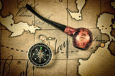 Tobacco pipe and compass on map — Stock Photo