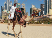A man riding a camel on the beach — Stock Photo