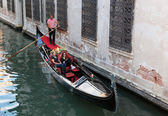 Tourists float in gondola on canal in Venice — Stockfoto