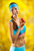 A sports girl holding an apple — Stock Photo