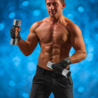 A muscular male with dumbbells — Stock Photo