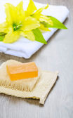 Flower on towel and soap on bast — Stock Photo