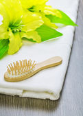 Hairbrush and flower on towel — Stock Photo
