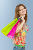A girl with paper bags looking at camera and smiling — Stock Photo