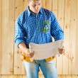 Carpenter looks on blueprint - Stock Photo